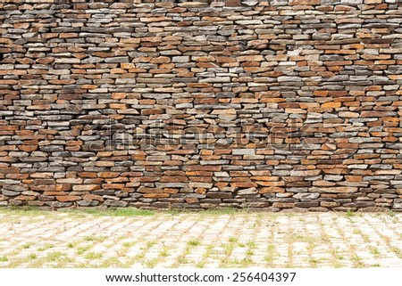 tiling stone wall. Sand stone and grass - stock photo