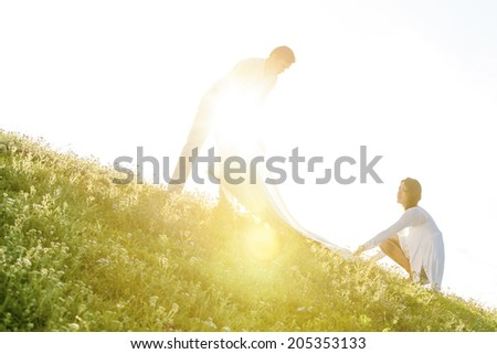 Tilt image of young couple spreading picnic blanket on grass during sunny day - stock photo
