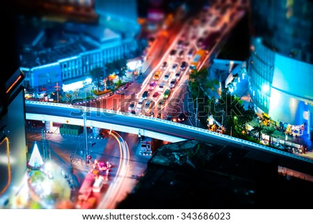 Tilt shift blur effect. Futuristic night cityscape aerial view panorama with illuminated skyscrapers and city traffic across streets. Bangkok, Thailand - stock photo