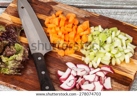 tilted view of a bamboo cutting board with chef's knife with freshly chopped organic carrots, lettuce, celery, and radishes - stock photo