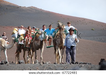 TIMANFAYA NATIONAL PARK, LANZAROTE, SPAIN - JUNE 10: Tourists ride on camels being guided by local people through the famous Timanfaya National Park in June 10, 2009 - stock photo