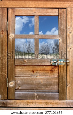 Timber door with window to landscape 1 - stock photo