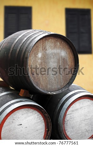 Timber storage barrels with blank space for copyspace text stack on its side in front of a rustic tavern. - stock photo