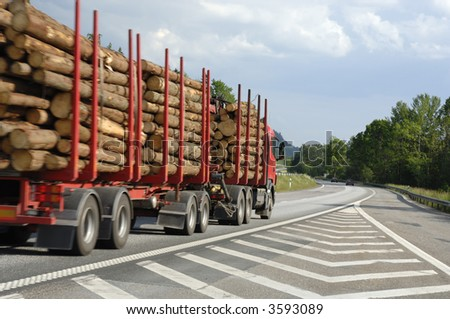 timber-truck on highway, driving past,  shot from ground level - stock photo