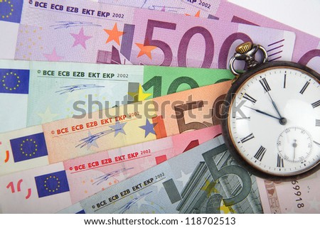 Time and Money concept image.  Close-up of  Euros  with vintage watch. - stock photo