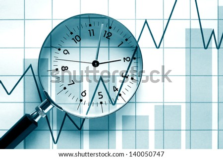 Time concept. Clock face inside magnifying glass on background with business chart - stock photo