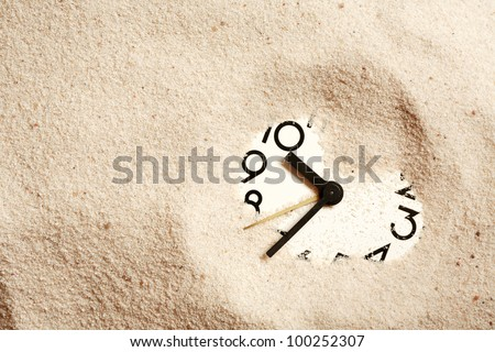 Time concept. Sand background with clock face - stock photo