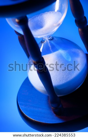 Time concept. White Sand Flowing through an Hourglass. Blue, White and Black Colors. - stock photo