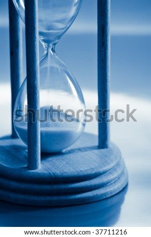 time concept with hourglass blue toned - stock photo