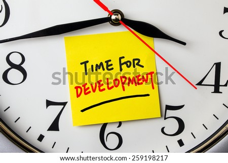 time for development on post-it stuck to a wall clock - stock photo