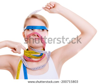 Time for diet slimming weight loss concept. Health care healthy lifestyle. Sport fit fitness woman with a lot of colorful measure tapes around her head. Obsessed girl.  isolated on white background - stock photo