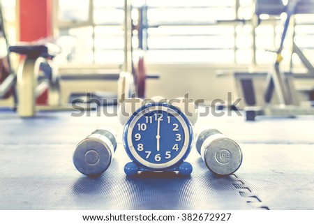 Time for exercising alarm clock and dumbbell  the Gym background. Share Time Exercise Healthy Concept - stock photo