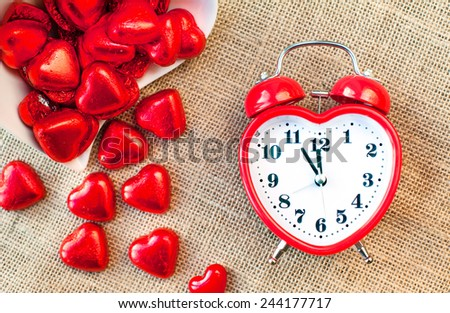 Time for love. Red heart shaped clock with many small sweet chocolates on burlap background. Indoors close up.  - stock photo