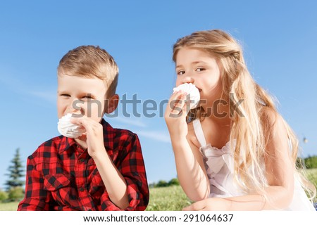 Time for meal. Nice little boy and girl sitting on the blanket and  eating marshmallow while evincing joy. - stock photo