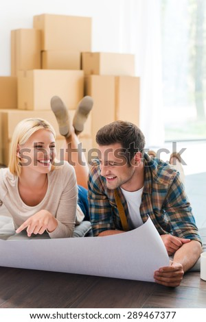Time for planning their new house. Happy young couple laying on the floor of their new apartment and looking through blueprint while cardboard boxes laying in the background - stock photo