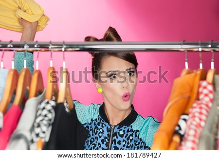 Time for refreshing wardrobe young attractive surprised woman searching for clothing in a closet  - stock photo