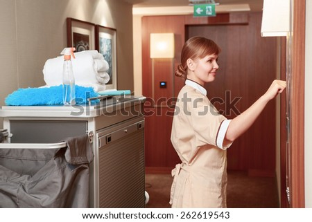 Time for room service. Smiling hotel maid in beige uniform knocking on the hotel room for room service by the maid trolley in the hotel hall - stock photo