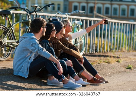 Time for selfie. Group of young smiling people bonding to each other and making selfie by smart phone while sitting outdoors together with bicycles in the background  - stock photo