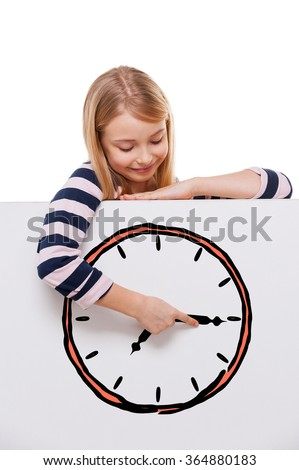 Time goes back. Cheerful girl leaning over white board with clock sketch on it and adjusting arrow while standing against white background  - stock photo
