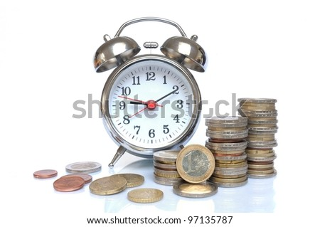 Time is money - Alarm clock and piles of Euro coins on white background - stock photo