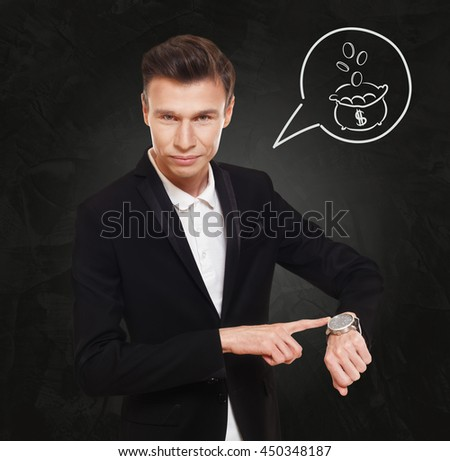 Time is money. Businessman point at his watch showing clock, cash flow concept. Man in suit at black background, thinking cloud with bag of coins. Work and earn, business, finance. - stock photo