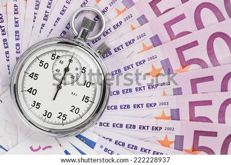 Time is money concept, analog stopwatch on the euro banknotes with copy space - stock photo