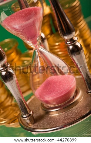Time is money concept - hourglass and coins - stock photo