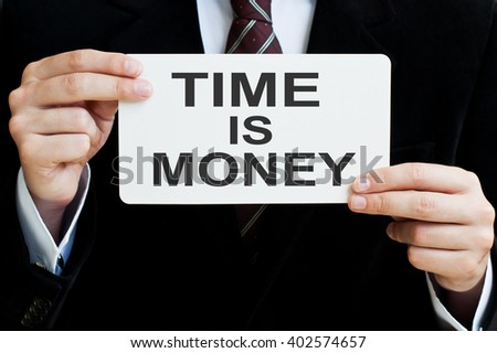 Time is Money concept. Man holding a card with a message text written on it. - stock photo
