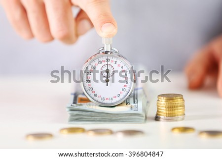 Time is money concept. Stopwatch  on the table with money, close up - stock photo