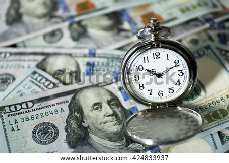 Time is money concept with pocket watch and dollars bills closeup - stock photo