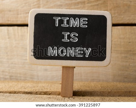 Time is money concept. Wooden sign on wood background - stock photo