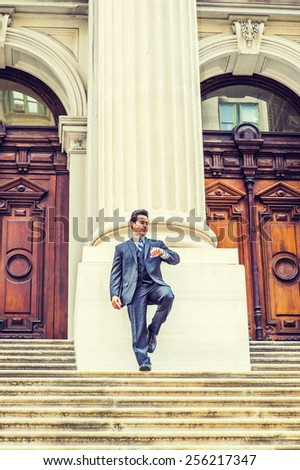 Time is Money. Dressing in dark blue suit, necktie, bending a leg, a handsome, sexy, middle age guy standing in front of office building, looking at watch, waiting for you. Instagram filtered look. - stock photo
