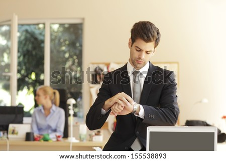 Time is money. Handsome businessman looking at his watch in office. Shallow focus.  - stock photo
