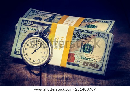 Time is money loan concept background - Vintage retro effect filtered hipster style image of stopwatch and stack of new 100 US dollars 2013 edition banknotes (bills) bundles on wooden background - stock photo
