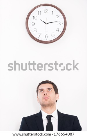 Time is money. Thoughtful young man in formalwear looking at the wall clock - stock photo