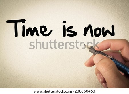 Time is now text write on wall  - stock photo