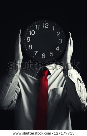 Time management. Businessman with clock in front of his head, deadline concept. Not enough time to finish the job. Selective saturation of a red tie. - stock photo