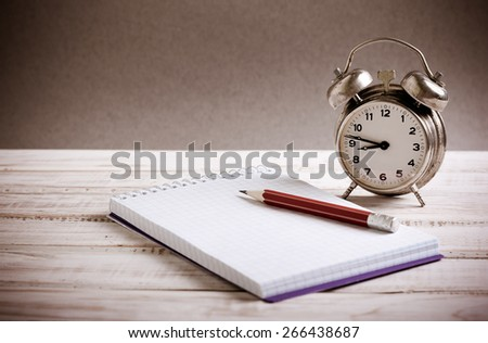 Time management concept: vintage alarm clock, pencil and notepad - stock photo