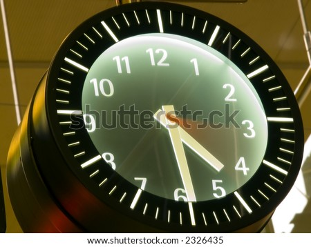 time passing by in a wall clock with blurred seconds hand - stock photo