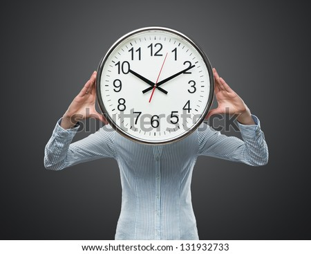Time pressure, close up of young businesswoman covering her face with analog clock isolated on gray background - stock photo