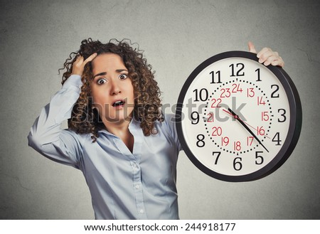 Time pressure. Closeup portrait woman stressed corporate employee holding clock looking anxiously running out of time isolated grey wall background. Human face expression emotion reaction. Last moment - stock photo