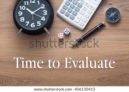 Time To Evaluate written on wooden table with clock,dice,calculator pen and compass - stock photo