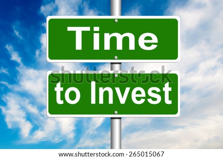 Time to Invest Road Sign with a blue cloudy sky in a background - stock photo