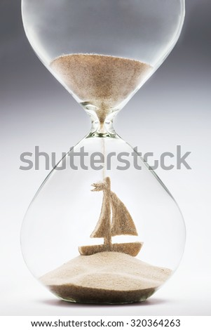 Time to make plans for summer vacation. Hourglass falling sand taking the shape of a sailing boat - stock photo