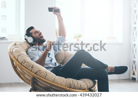 Time to relax. Handsome young man in headphones gesturing and keeping eyes closed while sitting in big comfortable chair at home   - stock photo