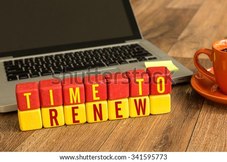 Time to Renew written on a wooden cube in a office desk - stock photo