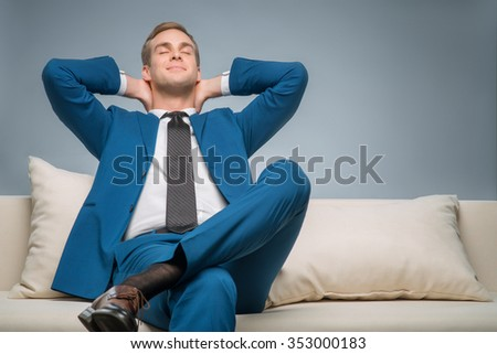 Time to rest. Smiling handsome businessman is sitting on the sofa and enjoying himself.  - stock photo