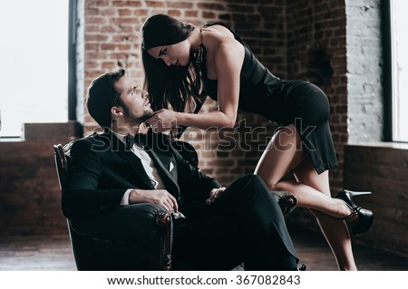 Time to seduce. Beautiful young woman in cocktail dress leaning to her boyfriend sitting in chair while looking at each other in loft interior - stock photo
