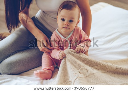 Time to start new day! Close-up part of little baby girl sitting on bed with her mother and pulling blanket - stock photo