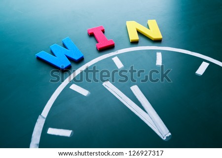 Time to win concept, color word and clock on blackboard - stock photo